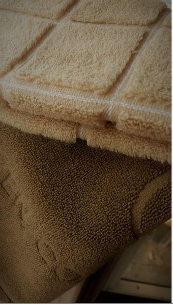 Liikkeessä otettu kuva keskiruskeasta lattiapyyhkeestä, päällä vertailun vuoksi beige (väri 277) pyyheliina.